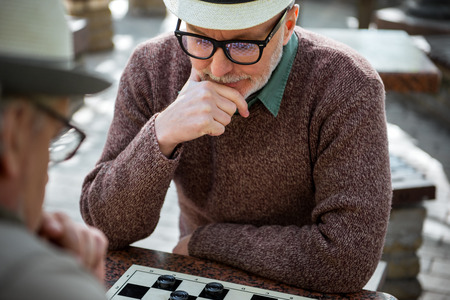 chequer: Mature male pensioner thinking about next move in checkers