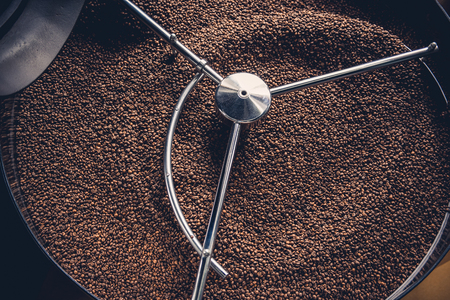 Top view close up aromatic coffee beans situating in spinning cooler professional machine. Arabica concept