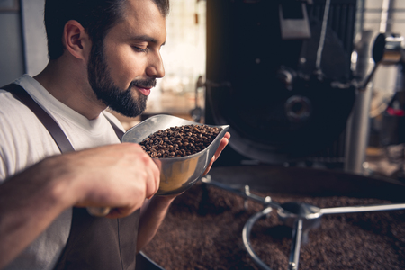 Side view smiling unshaven master smelling coffee grains while keeping them in ladle. He standing near industrial technical equipment. Factory concept Imagens