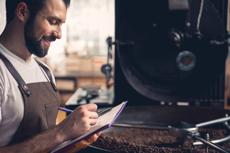 Side view smiling bearded man writing information about roasting beans in special equipment. Job concept
