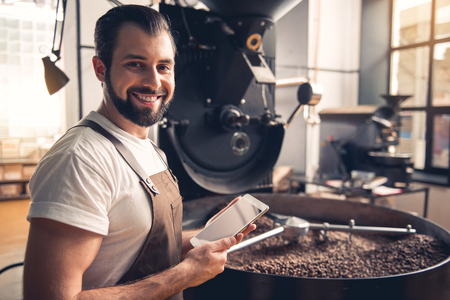Portrait of cheerful bearded worker using tablet while locating near coffee roaster with spinning cooler professional machine. Industry concept