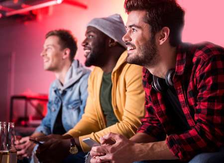 Comedy movie. Cheerful guys are watching tv at home. They are sitting on sofa and holding smartphone while looking at screen and expressing gladness. Focus on joyful man with headphones on his neck Stock Photo