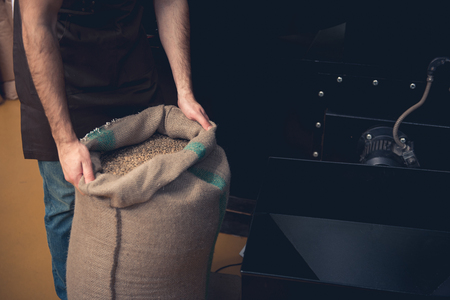 Close up male hands keeping huge sack full of brown seeds. Factory concept Stock Photo