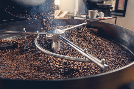 Aromatic coffee beans situating in modern equipment with grain chiller. Industry concept 免版税图像