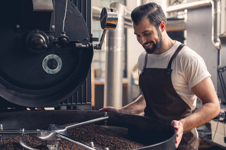 Portrait of happy young bearded man controlling coffee beans mixing in grain chiller. Control concept
