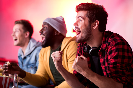Hooray. Happy young friends are screaming and expressing gladness while sitting on couch and watching match at home. Focus on pleasant stylish man with headphones on his neck Stok Fotoğraf - 89669261