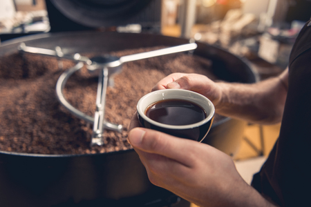Close up male hands keeping cup with delicious coffee near technical equipment. Rest concept