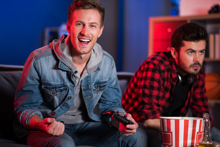 I am champion. Portrait of happy young guy is holding joystick and celebrating his win. He is sitting on sofa and expressing gladness while looking at camera with smile. His friend in background Stock fotó