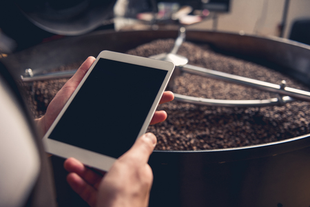 Close up male hand keeping tablet while having job at factory. He situating near technical equipment with coffee grains. Job concept Stock Photo