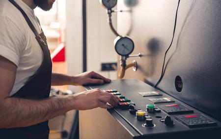 Barbu mâle maître appuyant sur le bouton sur un équipement spécial pour la création de café. Concept d'appareil technique. Gros plan de sa main Banque d'images - 89669608