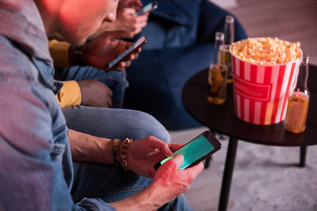 Useful gadget. Close-up of screen of mobile phone in hands of young man who is sitting on couch. He is sending message while resting with friends at home. Bottles of beer and popcorn are in background Banco de Imagens - 89669609