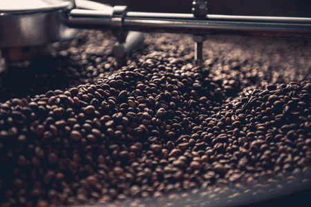 Close up aromatic coffee beans situating in professional machine with grain chiller. Prepare concept Stock Photo