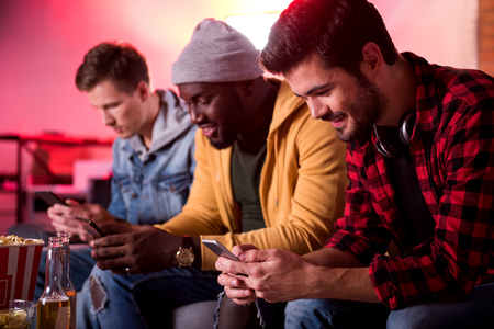 Cheerful news. Selective focus of joyful young man is sitting on sofa with mobile phone while looking at screen of gadget and expressing gladness. His friends are holding smartphone in background