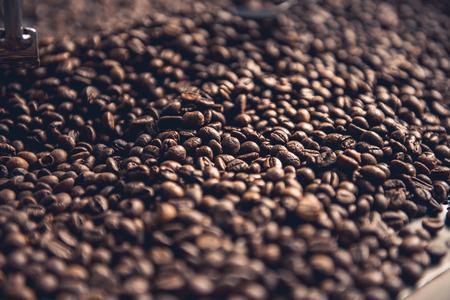 Ciérrese encima de los granos aromáticos marrones que colocan en el cilindro de enfriamiento. Concepto de preparación Foto de archivo - 89625726