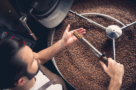 Top view serious bearded worker near coffee roaster controlling level of grain roasting. Revise concept