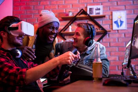Geniet van een driedimensionaal beeld. Blije jonge gamers lachen terwijl ze kijken hoe hun vriend speelt met een virtual reality-bril in autoraces met een videogame met stuur Stockfoto