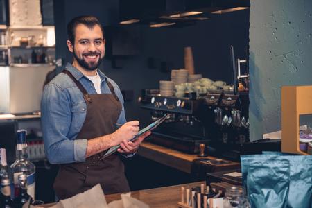 Portrait de joyeux travailleur mal rasé, écrivant des informations tout en gardant le presse-papiers à la main. Il se situant au comptoir d'un magasin de confiserie. Concept d'occupation Banque d'images - 89667086