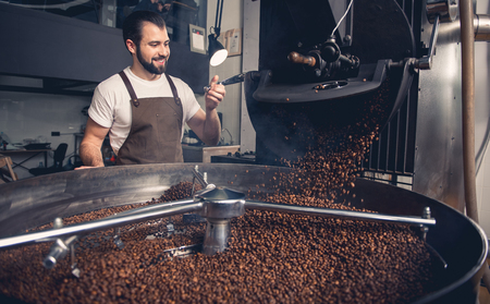 Portrait of cheerful bearded master having job at factory. He controlling brown beans pouring into cooler machine from large coffee roaster. Work concept Stock Photo