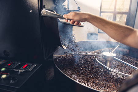 Man arm pressing button to open appliance. Coffee pouring from roaster machine to cooling cylinder. Industry concept. Close up Stock Photo