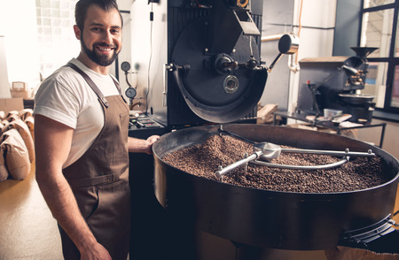 Portrait of happy unshaven male having job at factory. He controlling preparing coffee beans in roaster equipment. Occupation concept