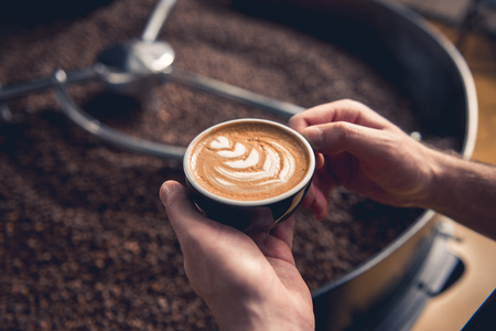 Focus on close up male hands holding cup with delicious cappuccino. Coffee grains situating in cooler machine at factory. Break concept