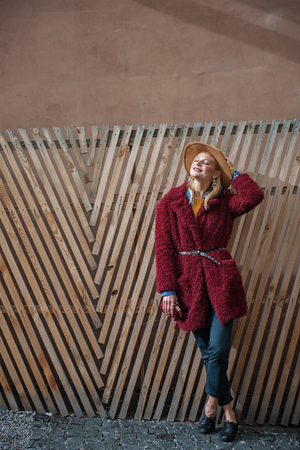 Enjoying fresh air. Full length portrait of fashionable young woman leaning on wooden fence and laughing. Her eyes are closed with pleasure. Copy space