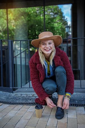 Retrato de la mujer joven alegre que ata cordones mientras que se arrodilla en la calle. Ella mira a la cámara y se ríe. La taza de café está en el callejón cerca de ella Foto de archivo - 90078954
