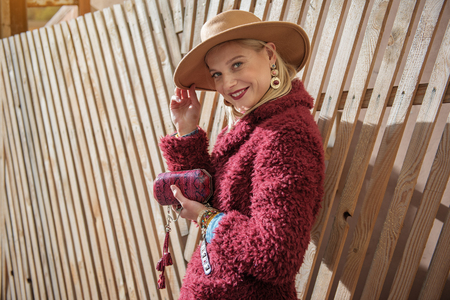 Always in trend. Portrait of self-sufficient young woman posing in stylish coat and hat. She is holding small wallet and smiling. Copy space Stock Photo