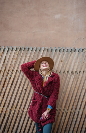 Wonderful weather for walking. Portrait of happy blond woman laughing while enjoying autumn sun. She is touching hat while standing near wooden fence. Copy space above