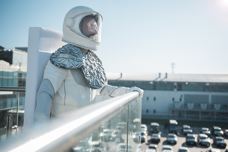 Cheerful spaceman wearing white armor is standing outside and looking forward with sincere smile. Profile. Copy space on right side Stock Photo