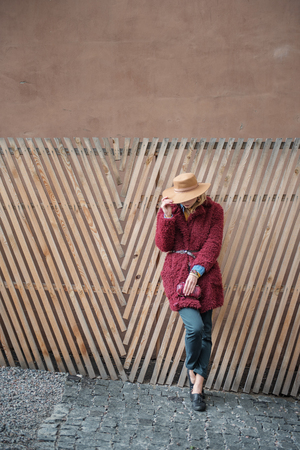 Full length of glamorous blond girl standing near wood fence while hiding face by trendy hat. She is carrying small purse. Copy space