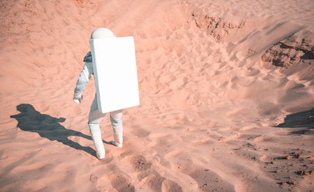 Spaceman wearing white armor is moving forward into desert. Focus on male back. Copy space on right side