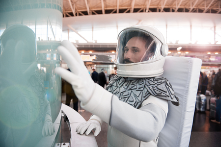 Curious man wearing white armor and helmet is standing near glass wall and looking with great interest. Waist up portrait. Copy space on left side