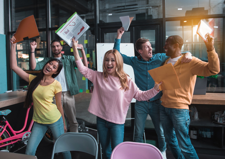 Stunning victory. Delighted young colleagues are rising their hands with documents up while celebrating finished of their successful project in office. They are screaming while feeling extremely happy Stok Fotoğraf