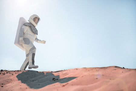 Astronaut wearing white armor is hardly move forward in desert. Low angle. Copy space on right side