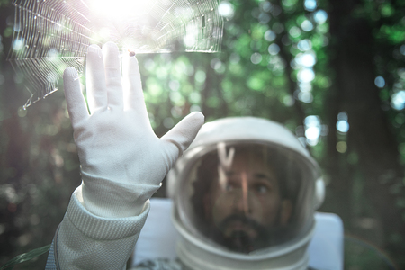Surprised spaceman is locating in forest. He touching to spider sitting on spiderweb. Copy space on right side Stockfoto