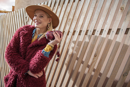 Portrait of confident blond woman standing on street and smiling. She is carrying small trendy clutch bag and looking at camera with joy. Copy space Stock Photo