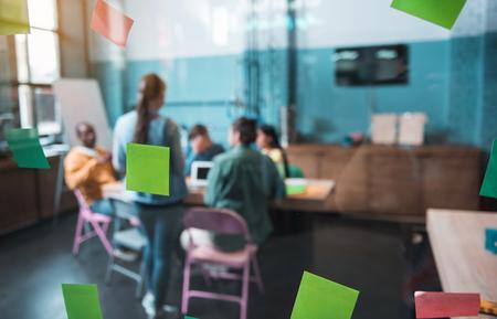 近代的なオフィスにデスクを置くことながら一緒に仕事を持つ若いスタートアップ チーム。カラフルなポスト ・ イット ノート ウィンドウ上で検索
