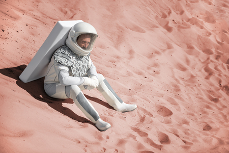 Mindful astronaut wearing white armor is sitting on sand and looking ahead with bewilderment. Copy space on right side Stock Photo
