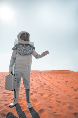 Under hot sun. spaceman is standing at red sand and holding suitcase. He looking aside with seriousness. Full length portrait. Copy space on right side
