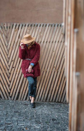 Full length of mysterious young woman covering her face by beige hat shyly. She is standing near wooden palisade on street in stylish coat