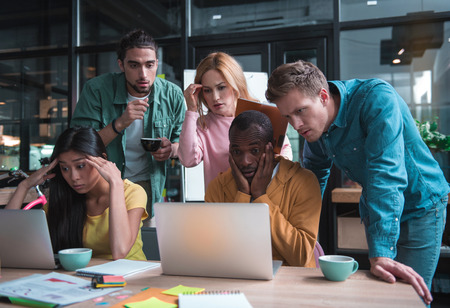 Feeling shock. Surprised worried young coworkers are looking at screen of laptops while keeping eyes wide opened and expressing consternation because of unexpected big mistake in their project