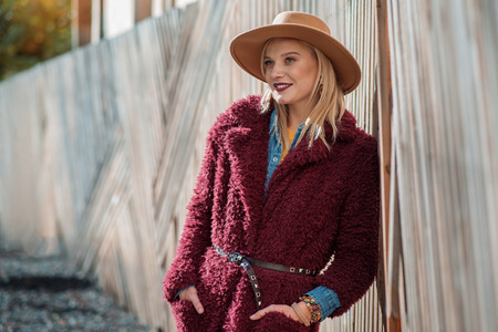 Portrait of carefree blond girl standing near wood palisade and relaxing. She is keeping hands in pockets of stylish coat and laughing. Copy space Stock Photo