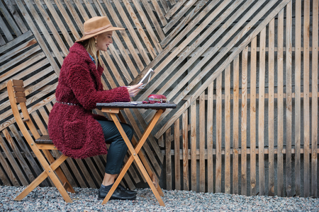 Side view profile of joyful young woman reading information in her notebook. She is sitting at table and smiling outdoor. Copy space
