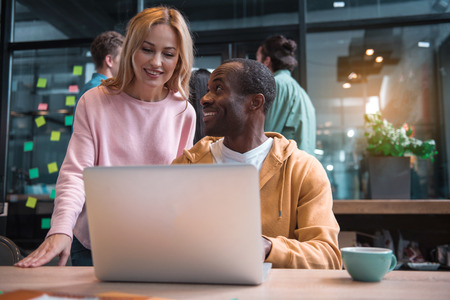 Let me see. Low angle of african man is sitting at table with laptop while gazing at young woman with smile. She is standing behind him and looking at screen while enjoying their cooperative work Stock Photo