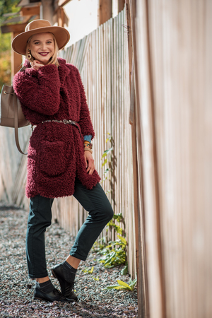 Always in style. Full length portrait of fashionable young woman standing near wooden palisade outdoor. She is carrying purse and smiling Stock Photo