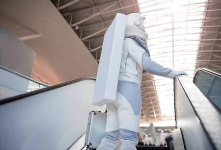 Spaceman wearing white armor is using escalator for rising to upper floor. Low angle. copy space on right side
