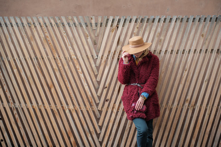 Stylish young lady posing in trendy red coat and hat. She is holding small clutch bag and leaning on wooden fence. Copy space
