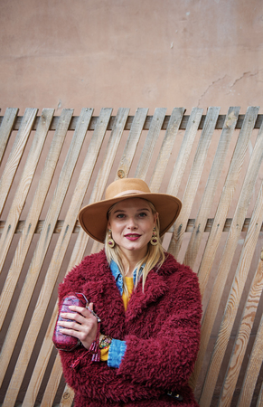 Waist up portrait of confident lady posing near wooden fence in fashionable coat and hat. She is looking at camera and smiling. Copy space above