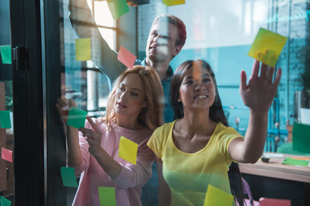 Portrait of cheerful young females and outgoing male gluing colorful stickers on glass in room. Idea concept